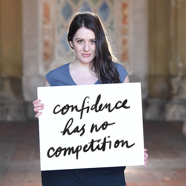 "Libby Rothschild holding a sign that says, ""Confidence has no competition"""